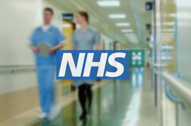 Two people walking down a hospital hall with the NHS logo.