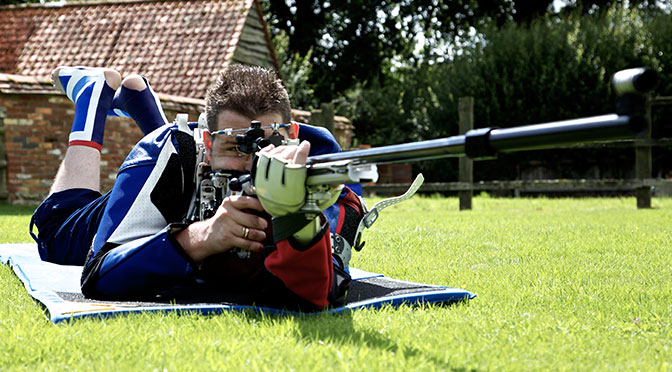 Ben Jasson lying on the grass with a rifle
