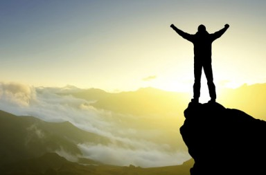 a man standing on the edge of a cliff with his arms in the air