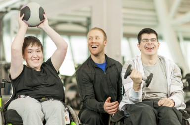 Disabled individuals with trainer working out.