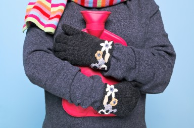 Photo of a woman holding a red hot water bottle to her chest whilst wearing hand kniited woolen gloves trying to keep warm, good image for winter illness or warmth related themes.