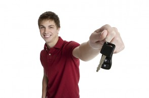 Attractive teenage boy holding car keys isolated on white backgr
