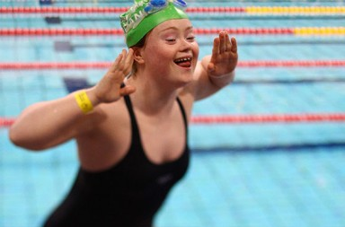 Woman with downs syndrome egging on the crowd at a swimming event.